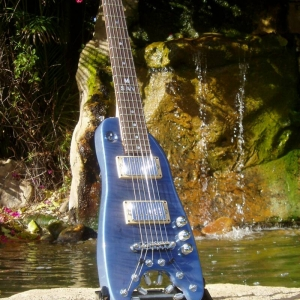 Pearly Blue Rambler Custom Travel Guitar by the waterfall