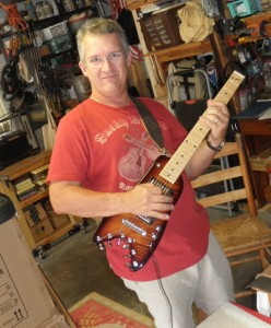 Scott picking up his Maple Neck Rambler Guitar