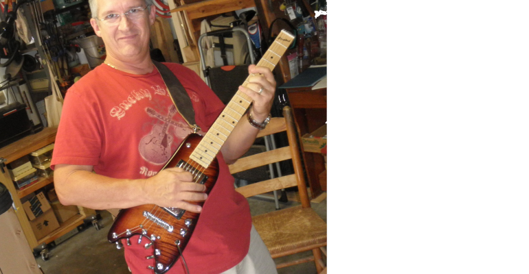 Scott picking up Maple Neck Rambler Travel Guitar