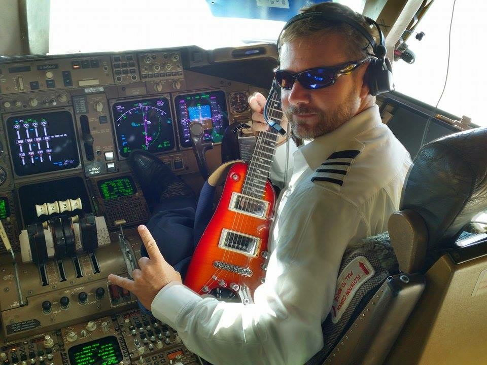 Capt. Buter in cockpit with his Rambler Travel Guitar